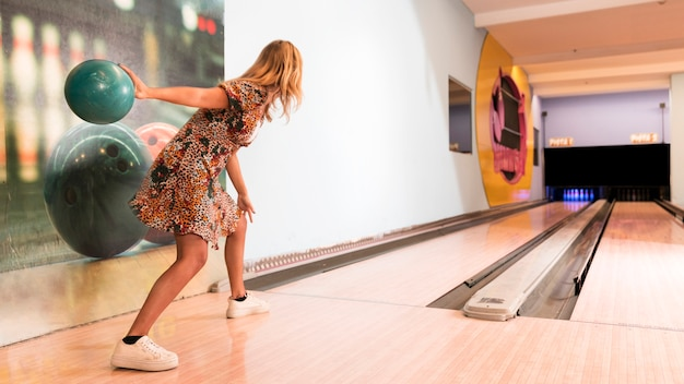 Back view woman throwing bowling ball Free Photo