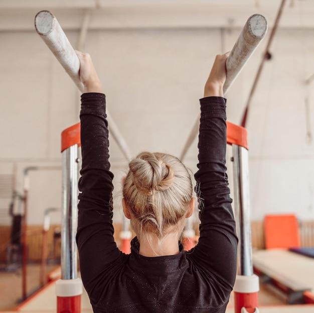 Вид сзади женщины, тренирующейся для чемпионата по гимнастике Бесплатные Фотографии