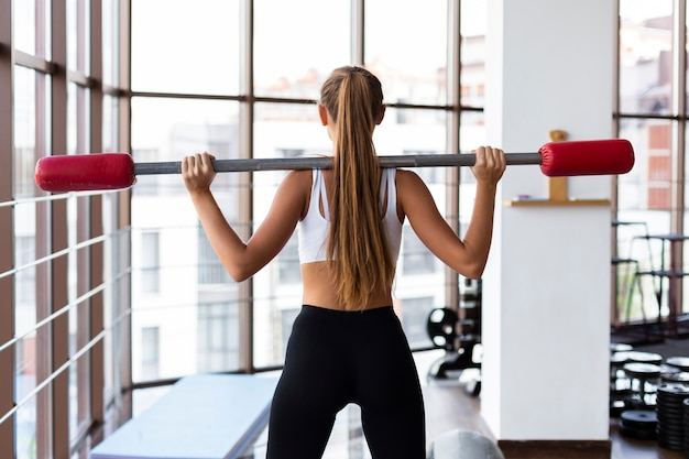 Back view of woman training with weights bar Free Photo
