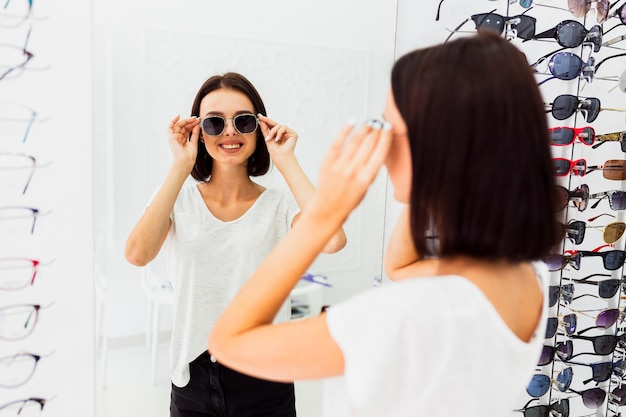 Back view of woman trying sunglasses Free Photo