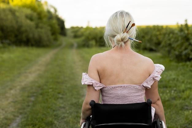 Vista posteriore della donna in sedia a rotelle all'aperto Foto Gratuite