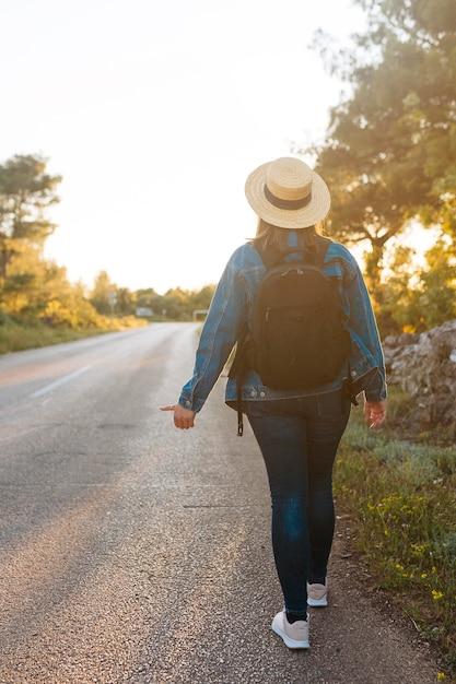 Punto di vista posteriore della donna con zaino autostop Foto Gratuite