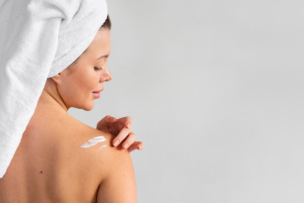 Back view of woman with towel on head applying cream on skin Free Photo