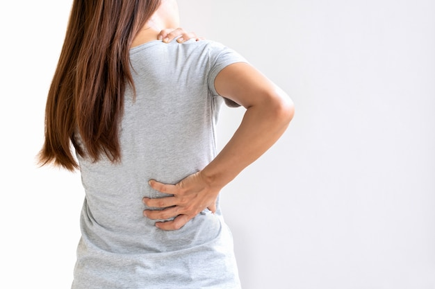 Back view of young asian woman suffering from backache and neck pain isolated on white background Premium Photo