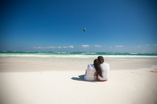 Back view of young couple sitting at tropical white beach Premium Photo