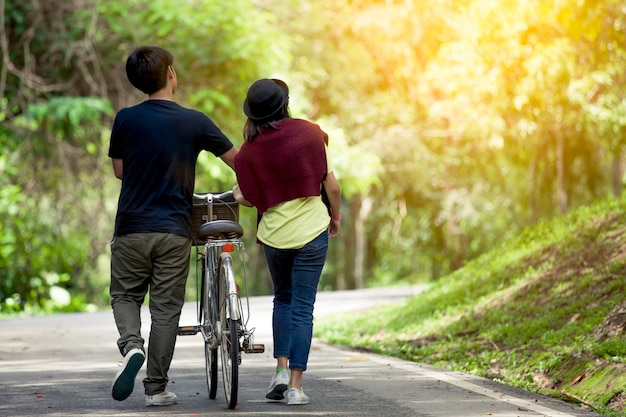 Back view of young couple walking  together with bicycle in the garden Premium Photo