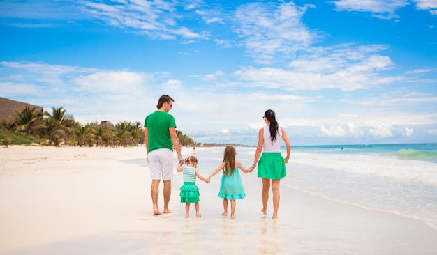 Back view of young family looking to the sea in mexico beach Premium Photo