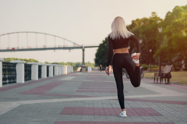Back view of a young fitness woman runner stretching legs before run outdoors Premium Photo