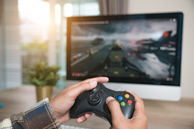 Back view of young gamer playing fps video games at home Premium Photo