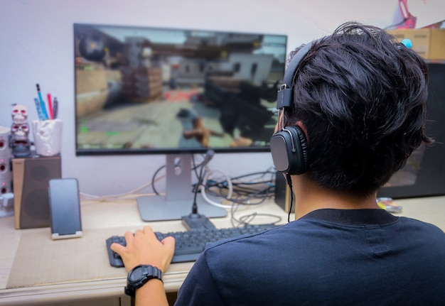 Back view of young gamer playing fps video games Premium Photo