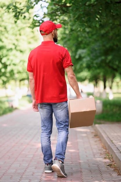 Vista posteriore giovane consegna scatola di cartone Foto Gratuite