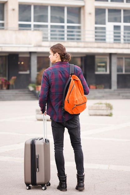Back view young tourist with luggage Free Photo
