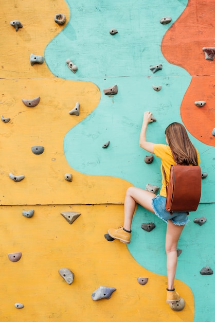 Back view young traveller climbing wall Free Photo