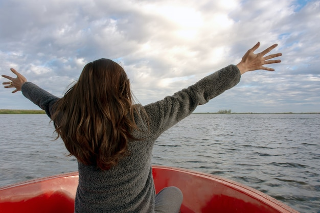 Back view of the young woman extending arms and enjoy on the boat and looking forward into lagoon Premium Photo