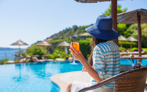 Back view of young woman sitting in tropical cafe near swimming pool Premium Photo