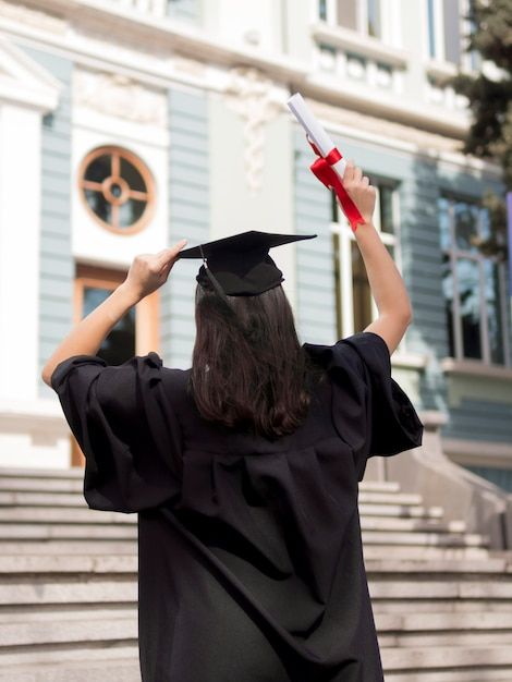 Back view young woman wearing graduation gown outdoors Premium Photo