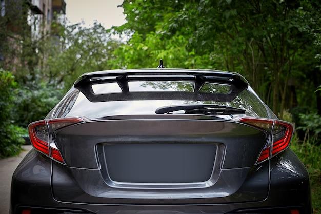 夏の晴れた日、背面に路上駐車した黒い車の後ろの窓。ステッカーやデカールのモックアップ Premium写真