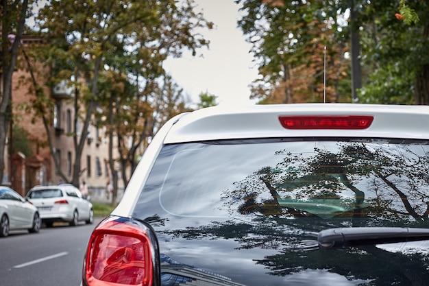 夏の晴れた日、リアビューで路上駐車していた白い車の後ろの窓。ステッカーやデカールのモックアップ Premium写真