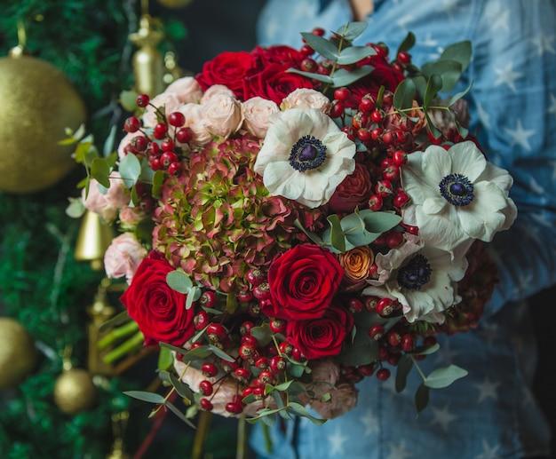 クリスマス装飾壁backgorundの手で秋の色の花の花束を保持している女性。 無料写真