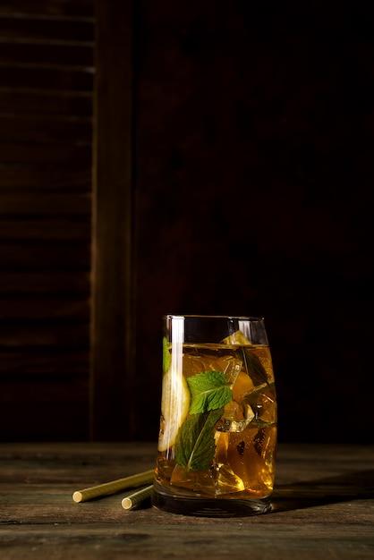 Коктейльное стекло со льдом, мятой и имбирем на темном деревянном backgorund Premium Фотографии