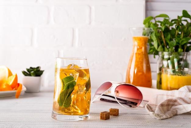 Коктейльное стекло со льдом, мятой и имбирем на белом деревянном backgorund Premium Фотографии