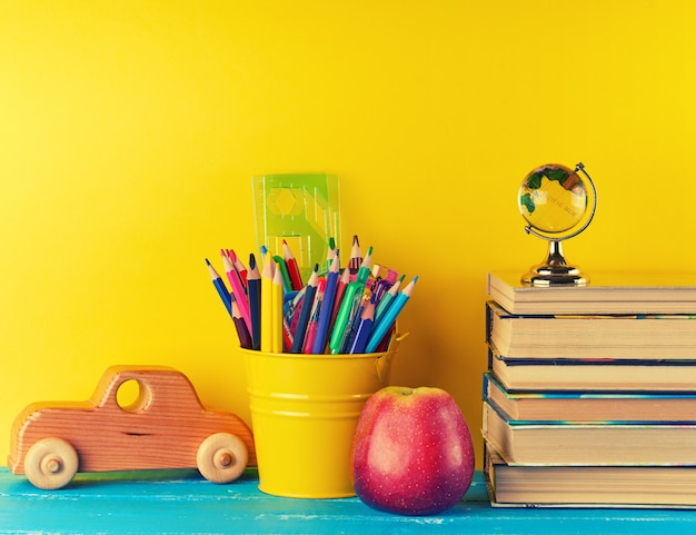 Background back to school with children stationery pencils, books, apple, glass globe Premium Photo