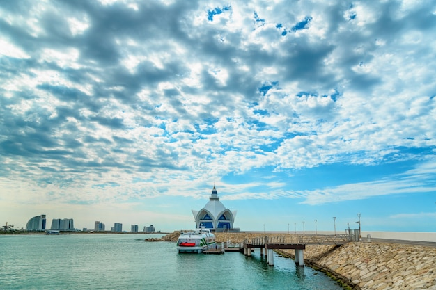 Background of blue sky with beautiful clouds and azure sea with marina in the frame Premium Photo
