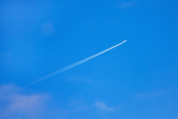 On the background of a clean blue sky, a plane fires away, leaving behind a clear white trail Premium Photo