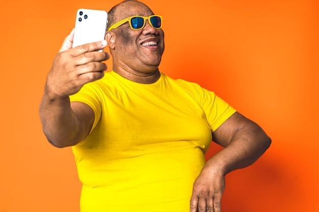 孤立したbackground.concept技術と高齢者のコミュニケーションに携帯電話を使用して幸せな黒人男性 Premium写真