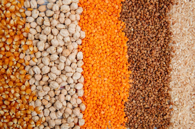 Background of different types of groats corn seeds chickpeas red lentils buckwheat and rice top view Free Photo