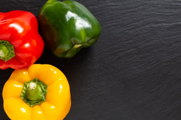 Background for food product 3 colors red green and yellow of organic bell pepper or parpika on black slate board Premium Photo