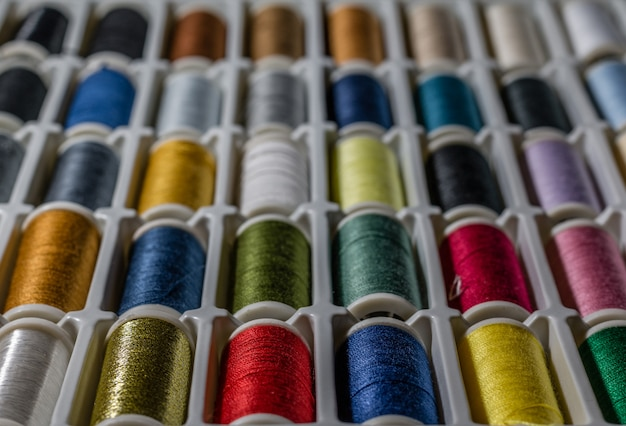 Background from bobbins with multicolored thread for sewing Premium Photo