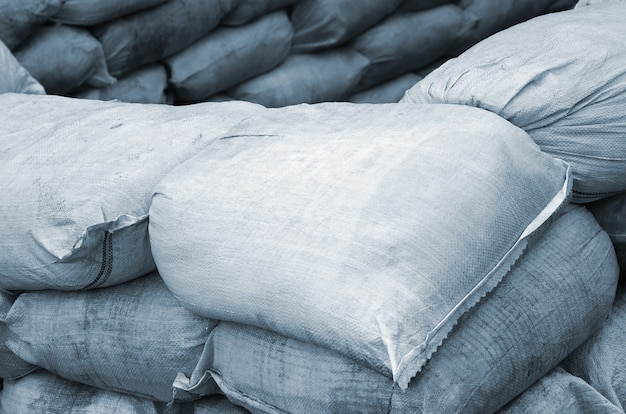 Background of many dirty sand bags for flood defense. Premium Photo