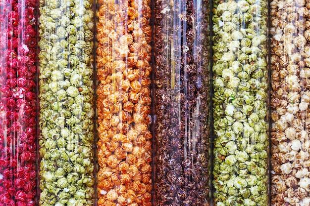 Background of multi-colored popcorn. red, yellow green, orange popcorn in glass container. Premium Photo