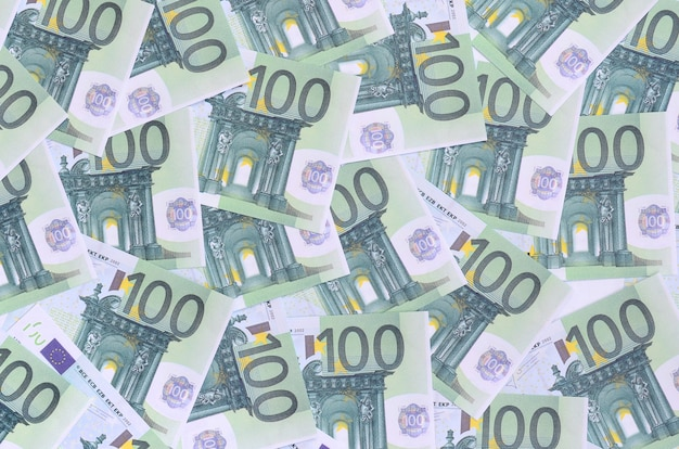 Background pattern of a set of green monetary denominations of 100 euros. a lot of money forms an infinite heap Premium Photo