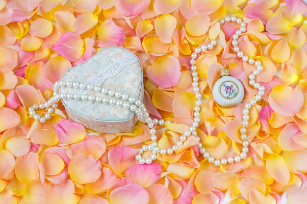 Background of pink rose petals, jewelry box, pearl beads and a bottle of perfume Premium Photo