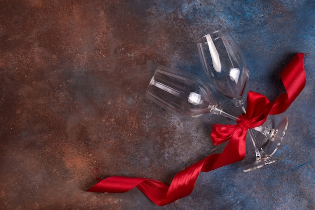 Background of valentines day celebration with two glasses and red ribbon Premium Photo