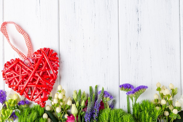 Background with spring flowers and decoratiove wooden heart Premium Photo