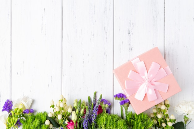 Background with spring flowers and pink gift box Premium Photo