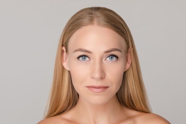 肯定的な感情を白いスタジオbackgroundavingで分離された美しい若いヨーロッパ女性の媒体のクローズアップの肖像画 Premium写真