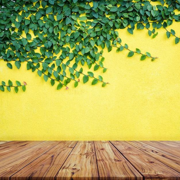 黄色のコンクリート壁backgroundignの緑の葉と空の木製テーブルトップ Premium写真