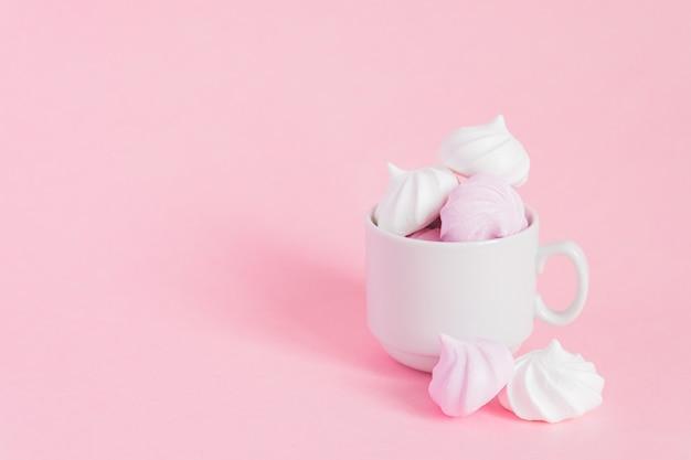 ピンクbackgroundwithコピースペースに小さな磁器コーヒーカップに白とピンクのツイストメレンゲ Premium写真