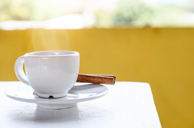 Белая чашка кофе на белом столе с желтым backgrund Premium Фотографии