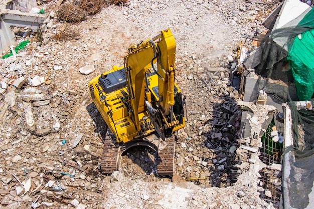 The backhoe machinery working on site demolition of an old building. Premium Photo