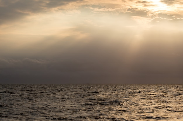 Backlit of sea and the sky with the light of the sun shines down impact. Premium Photo