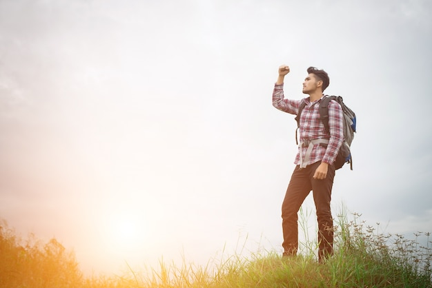 Backpacと手を上げ屋外若いヒップスターの男の肖像 無料写真