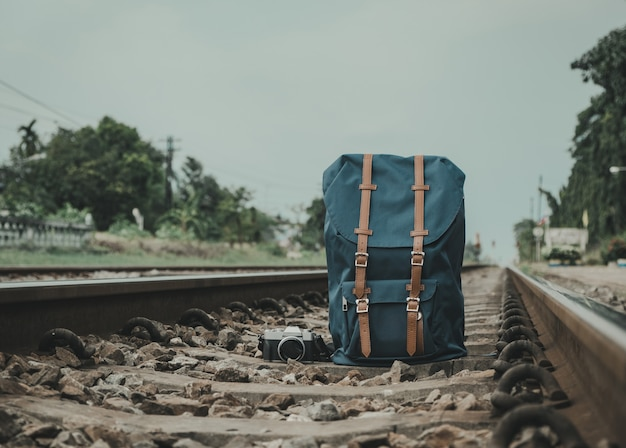 Backpack, camera, placed on the tracks to the travelers. vintage style. Premium Photo