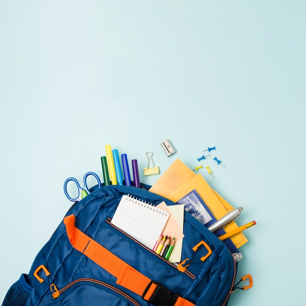 Backpack full of school accessories Free Photo