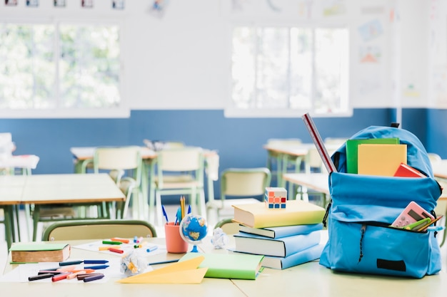 Backpack and stacked books on desk in empty classroom Free Photo