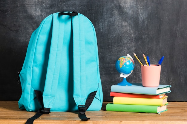 Backpack with books and globe Free Photo